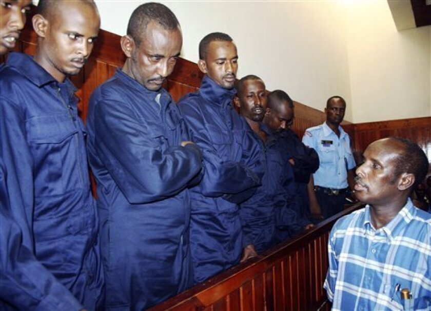 Some of the eight suspected Somali pirates listen as a translator Mohammed Ali Mohammed translates the proceedings of the day at the Law Courts in Mombasa Kenya Thursday Dec. 11, 20008, during the hearing of their case where they are charged with hijacking a cargo ship along Somali waters. The hearing of the eight Somali suspects was adjourned until January 14th,15th and 16th after the state pleaded for more time to go through the suspects files.. (AP Photo)