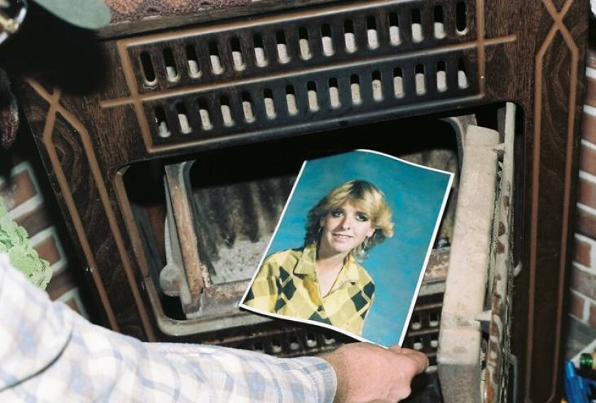 his undated photo provided by the Yavapai County Sheriff's Office shows a law enforcement official discovering a photograph of Pamela Pitts in the wood stove of a home she shared with two others in Prescott, Ariz., in 1988. Pitts' then-roommate, Shelly Harmon, recently confessed to killing Pitts and was sentenced to time she already had served in another killing. (Yavapai County Sheriff's Office via AP)