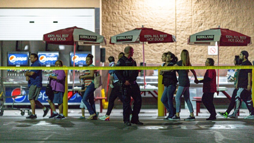 Customers are escorted from a Costco store in Corona after Friday night's shooting involving an off-duty LAPD officer.