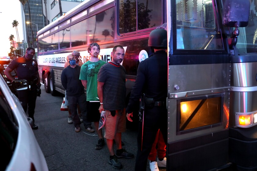 Protesters arrested for violating curfew are loaded onto a bus.