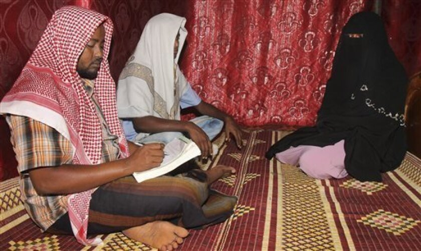 In this photo taken Wednesday, March 13, 2013, Abdi Ali, 25, center-left, and his girlfriend Anisa, 23, right, sit with an Islamic cleric, left, who marries eloping couples, during their elopement marriage in Walaweyn, Somalia. Since the Islamic extremist rebels of al-Shabab have been pushed out of