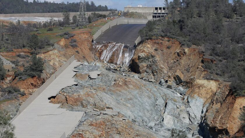FILE- In this Feb. 28, 2017 file photo, a small flow of water goes down Oroville Dam's crippled spil