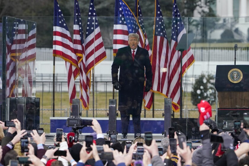 President Trump speaks onstage at a rally Wednesday behind bulletproof glass flanked by U.S. flags in front of supporters.