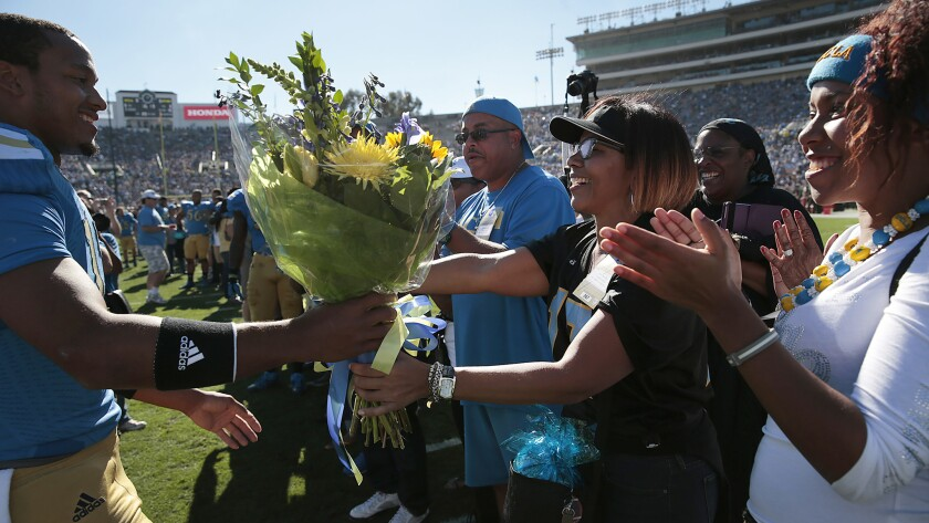 UCLA quarterback Brett Hundley, left, gives a bouquet of flowers to his mother, April, while greeting his family during the Bruins' senior day ceremony at the Rose Bowl on Nov. 28.
