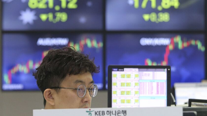 A currency trader watches monitors at the foreign exchange dealing room of the KEB Hana Bank headquarters in Seoul on Monday.