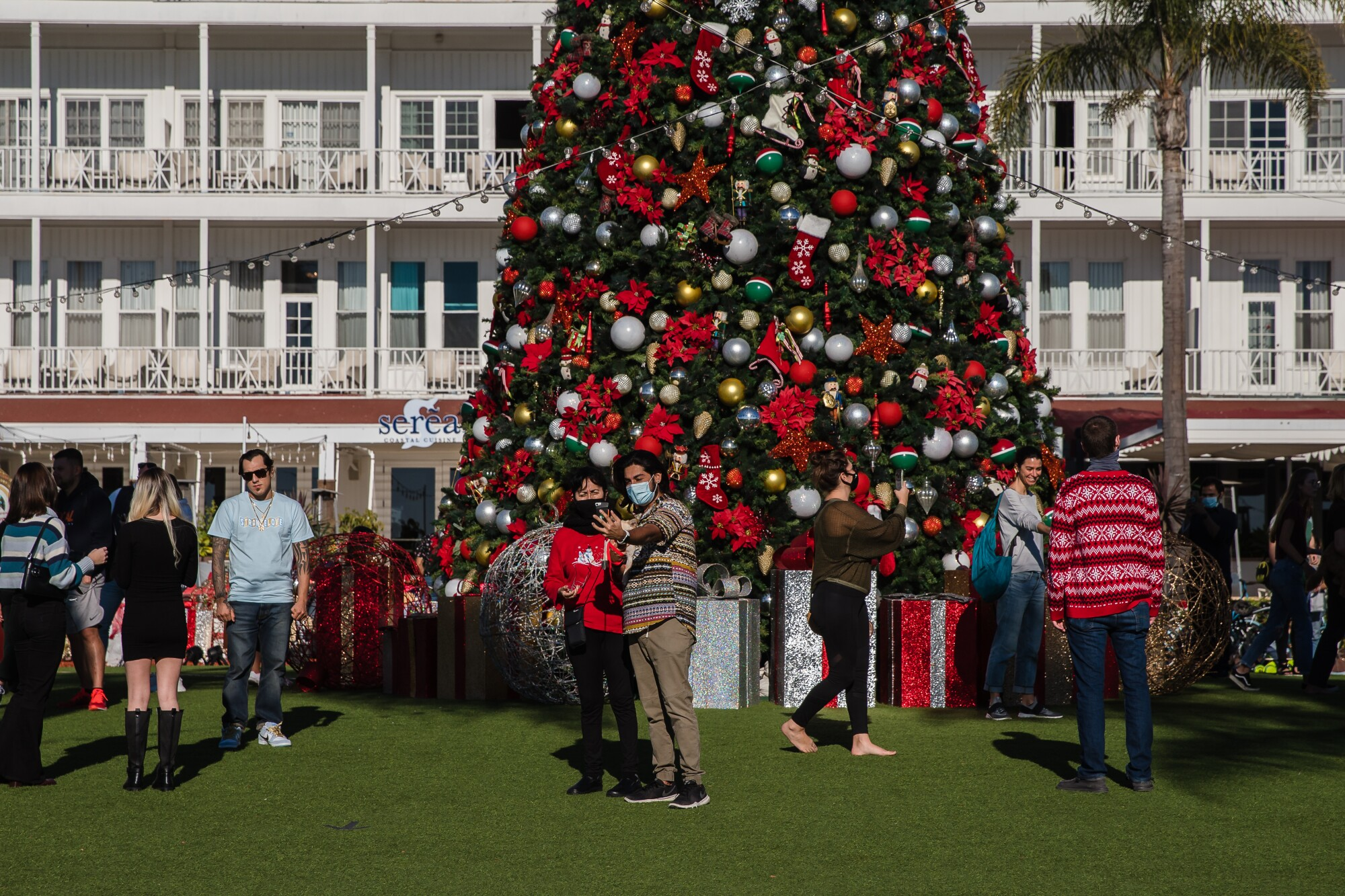 People around the Christmas tree at Hotel del Coronado on December 25, 2020.