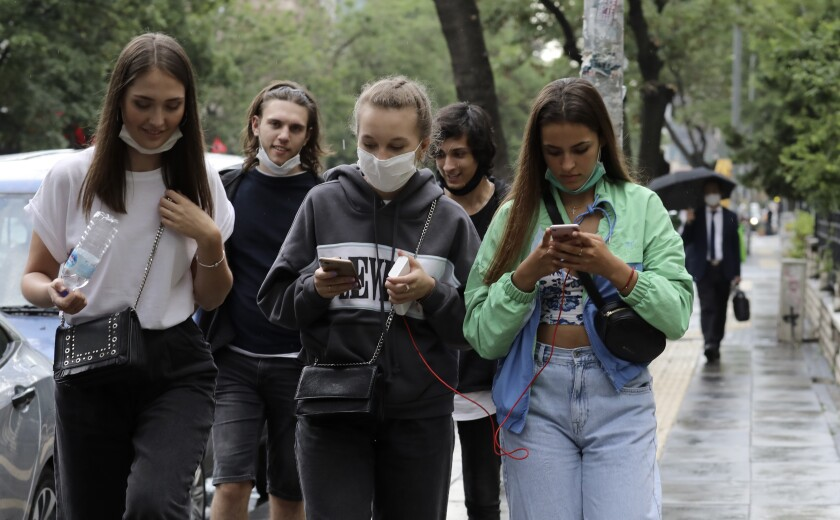 People walk in a popular street, in Ankara, Turkey, Wednesday, June 17, 2020. Turkey has made the wearing of face masks mandatory in five more provinces, following an uptick in COVID-19 cases. Health Minister Fahrettin Koca tweeted Tuesday that the wearing of masks is now compulsory in 42 of Turkey's 81 provinces.(AP Photo/Burhan Ozbilici)