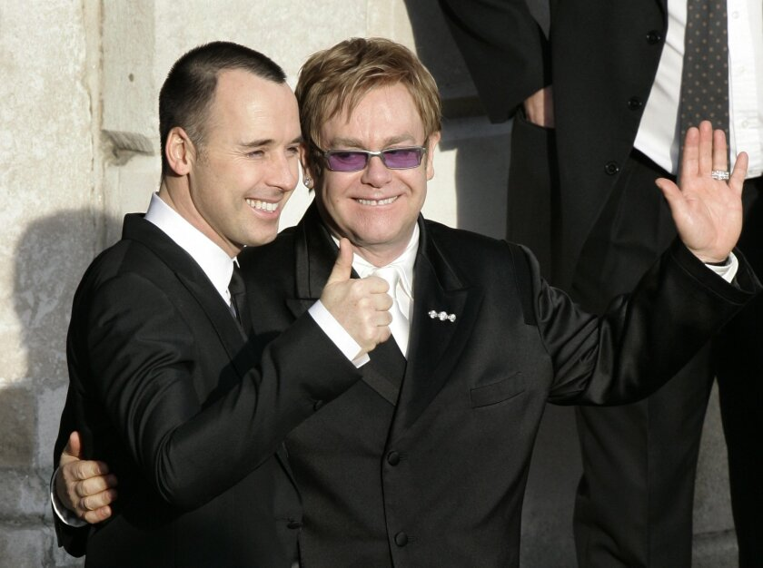 "FILE - This Wednesday Dec. 21, 2005 file photo shows Elton John, right, and his longtime partner David Furnish embrace as they wave to members of the media and the public after they had a civil ceremony at the Guildhall in the town of Windsor, England. The British government says the country's first same-sex weddings can be held on Saturday, March 29, 2014. Equalities Minister Maria Miller announced Tuesday Dec. 10, 2013 that marriage ""will be open to everyone, irrespective of whether they fall in love with someone of the same sex or opposite sex."" (AP Photo/Lefteris Pitarakis, File)"