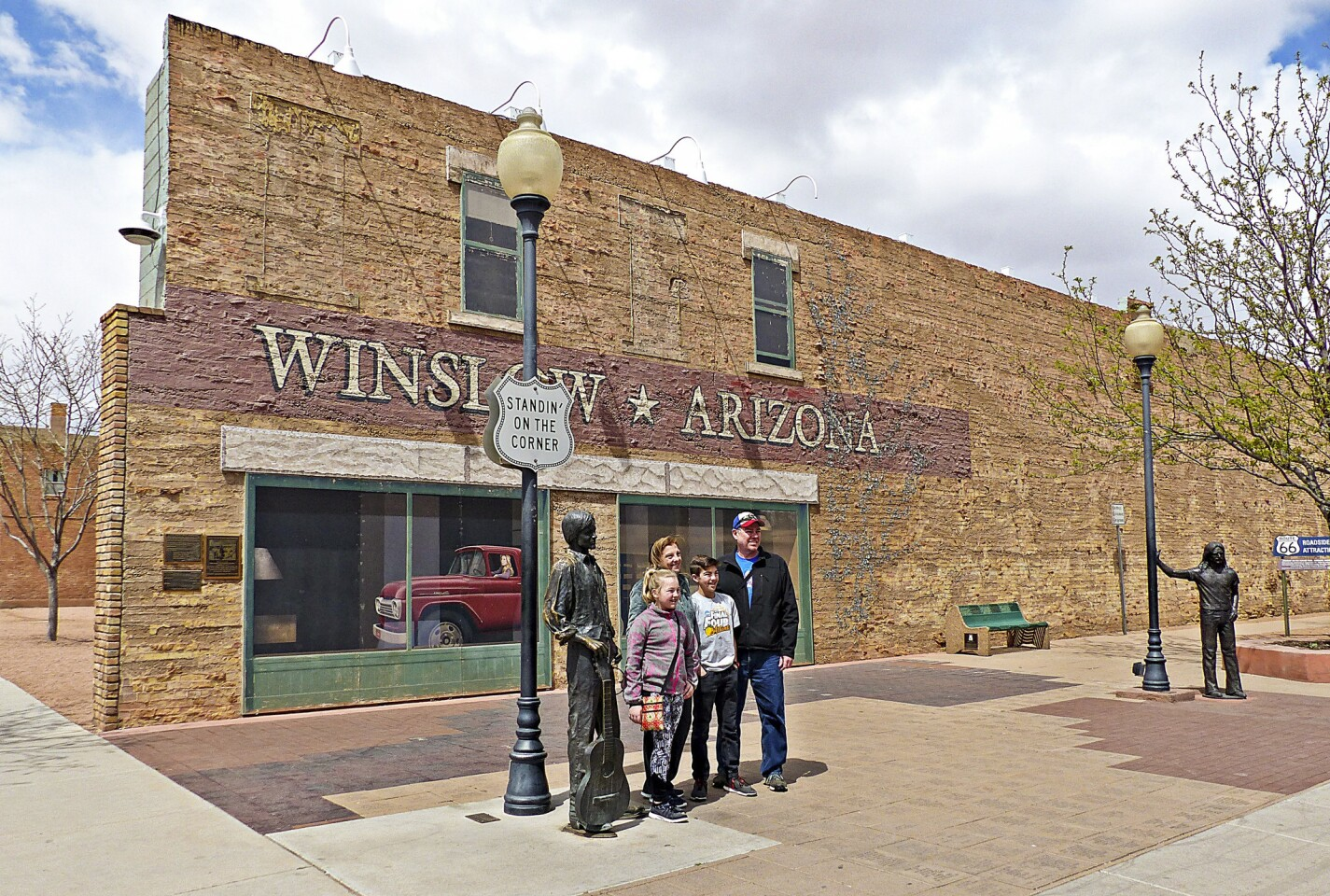 """On a corner in Winslow, Ariz., two blocks from the La Posada hotel, visitors snap photos, nostalgically recalling the popular 1970s song """"Take It Easy,"""" written by Glenn Frey and Jackson Browne and recorded by Frey and his Eagles bandmates."""