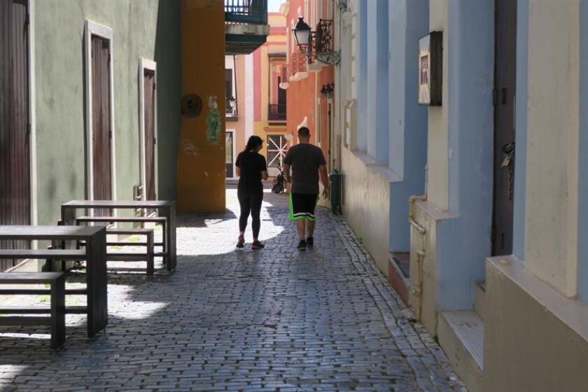 Dos personas caminan frente al Nuyorican Café ubicado en uno de los callejones del Viejo San Juan (Puerto Rico). EFE/Archivo