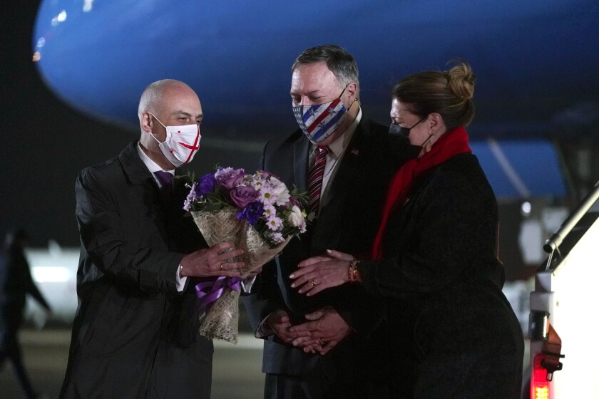 Georgian Foreign Minister David Zalkaliani, left, gives flowers to Susan Pompeo as she and her husband, Secretary of State Mike Pompeo, arrive at Tbilisi International Airport in Tbilisi, Georgia, Tuesday, Nov. 17, 2020. (AP Photo/Patrick Semansky, Pool)
