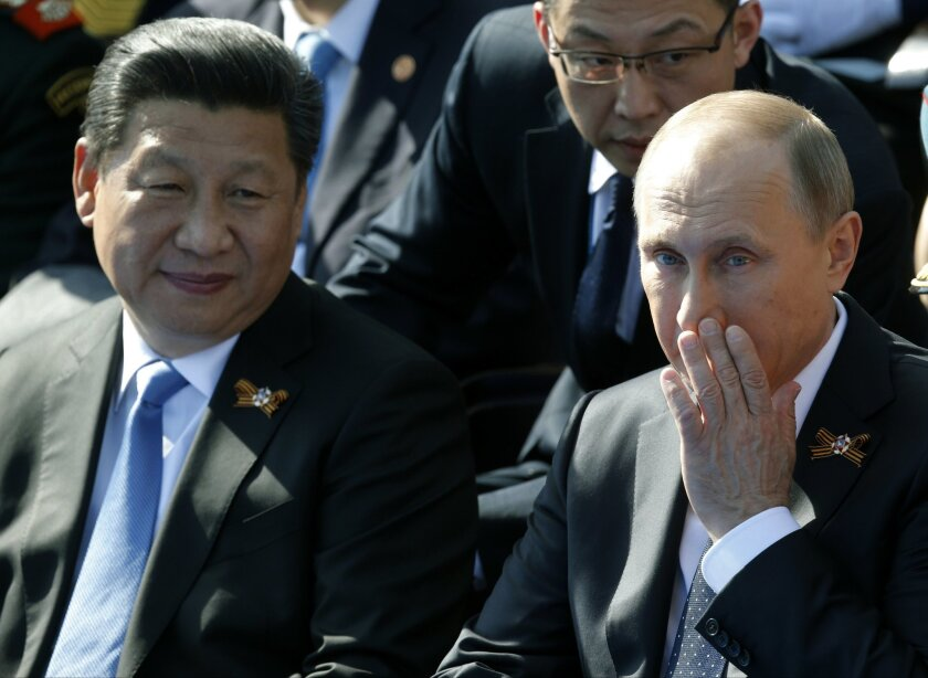 Russian President Vladimir Putin, right, and Chinese President Xi Jinping watch the Victory Parade marking the 70th anniversary of the defeat of the Nazis in World War II, in Red Square, Moscow, Russia, Saturday, May 9, 2015. (AP Photo/Alexander Zemlianichenko, pool)