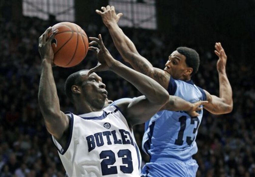 Butler forward Khyle Marshall (23) shoots after grabbing a rebound under Rhode Island guard T.J. Buchanan in the first half of an NCAA college basketball game in Indianapolis, Saturday, Feb. 2, 2013. (AP Photo/Michael Conroy)