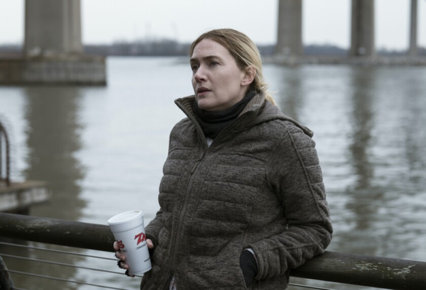 """Kate Winslet wears a winter coat and holds a Styrofoam cup beside a river in a scene from """"Mare of Easttown."""""""