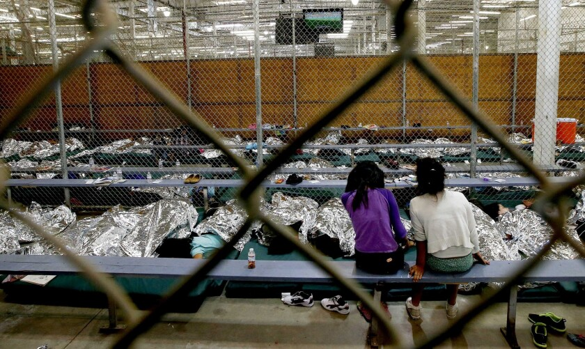 Two girls watch a World Cup soccer match on TV on June 18 at a center in Nogales, Ariz., where hundreds of mostly Central American immigrant children are being processed and held.