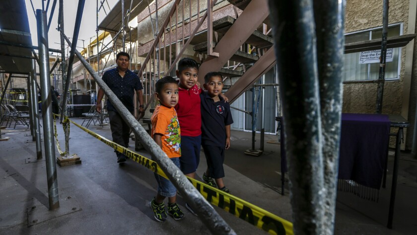 Brothers, Mathew Rosales, 3, left, Emiliano, 5, and Rudy Jr., 7, accompanied by their father Rudy Rosales, 34, pass between scaffolds in the court yard of Marmion Royal apartments in Highland Park.