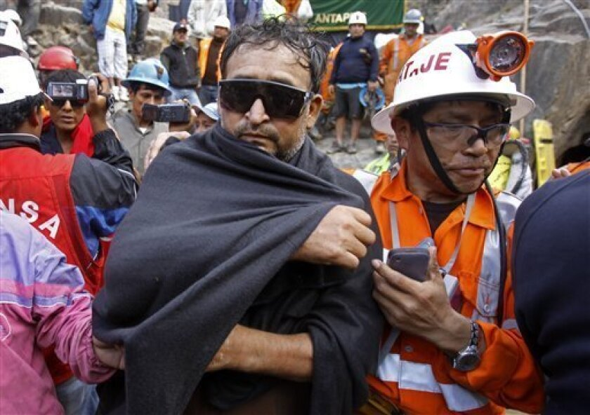 An unidentified miner, left, is helped by an emergency worker after being rescued from the Cabeza de Negro gold-and-copper mine in Yauca del Rosario, Peru, Wednesday April 11, 2012. Nine miners had been trapped inside a wildcat mine since April 5. (AP Photo/Martin Mejia)