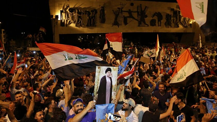 Followers of Shiite cleric Muqtada al-Sadr, displayed on the poster, celebrate in Tahrir Square, Bag