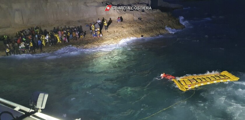 The Italian Coast Guard uses an inflatable raft to rescue migrants stuck on the shore of the Isola dei Conigli island off the Sicilian island of Lampedusa, southern Italy, Thursday, Sept. 9, 2021. The Italian Coast Guard rescued 125 migrants trapped on the rocks due to rough seas. (Italian Coast Guard via AP)