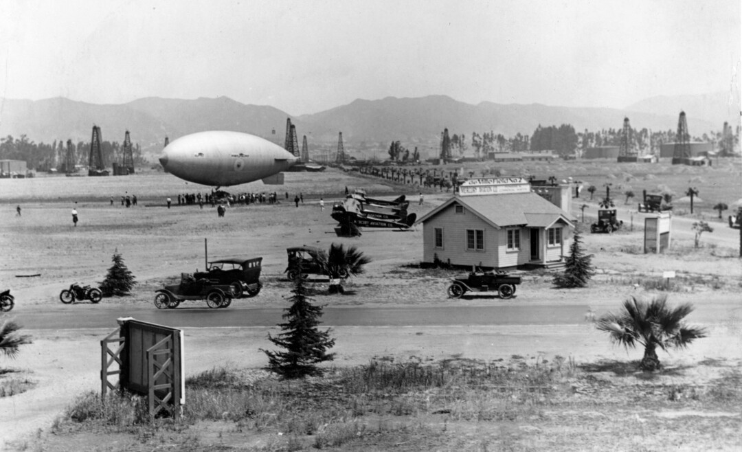 A vintage black and white photo shows a zeppelin in an airfield with oil derricks and mountains in the background