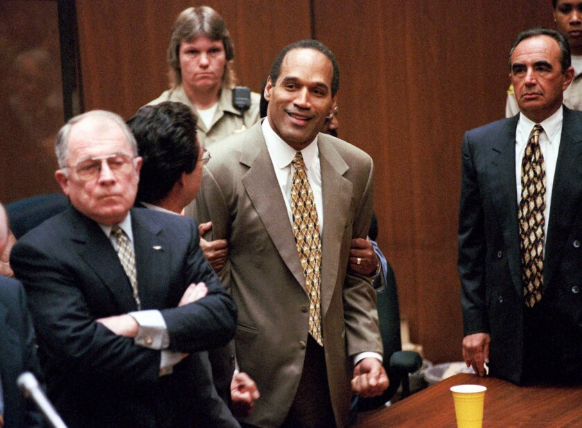 FILE - In this Oct. 3, 1995 file photo, O.J. Simpson, center, clenches his fists in victory after the jury said he was not guilty in the murders of his ex-wife Nicole Brown Simpson and her friend Ronald Goldman in a Los Angeles courtroom as attorneys F. Lee Bailey, left, and Robert Shapiro,  right,