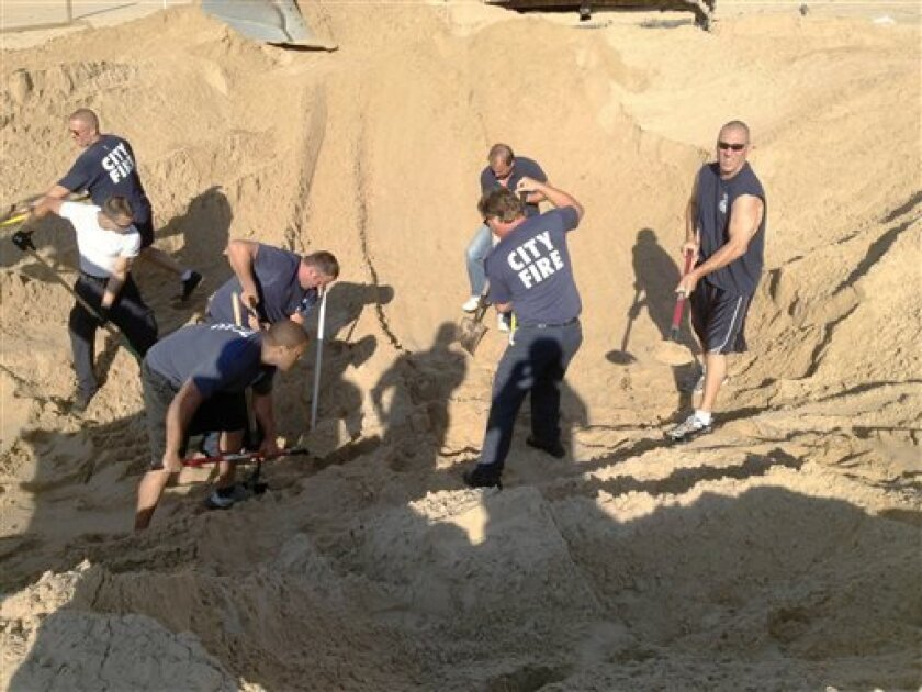FILE - In this July 12, 2013 file photo, Michigan City police and firefighters dig with shovels to rescue Nathan Woessner, of Sterling, Ill., who was trapped for more than three hours under about 11 feet of sand at Mount Baldy dune near Michigan City, Ind. The National Park Service and the Environmental Protection Agency will use ground-sensing equipment starting Monday, Aug. 12, 2013 to investigate Mount Baldy, a 43-acre sand dune at the Indiana Dunes National Lakeshore. That section of the par