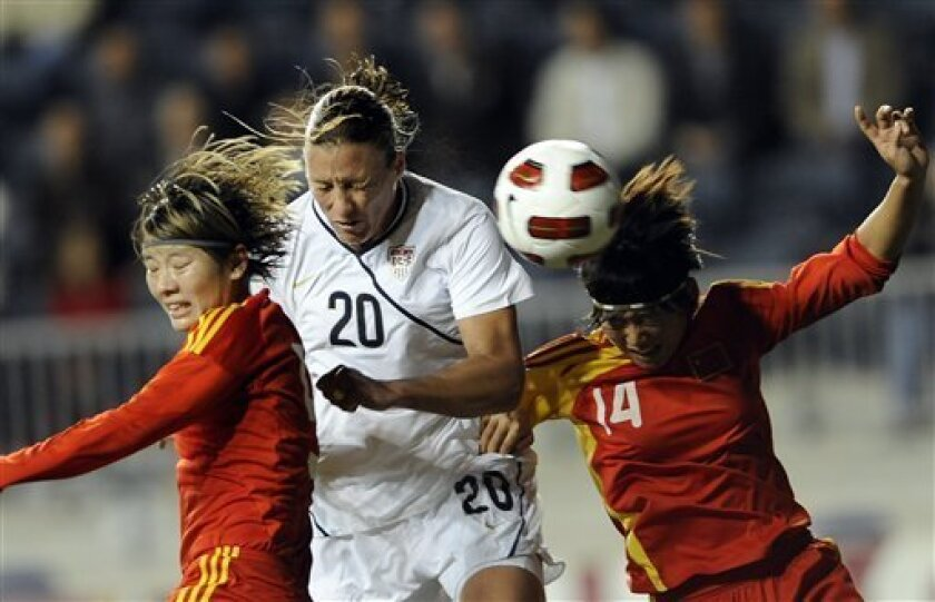 United States forward Abby Wambach (20) heads the ball past China defenders Li Danyang (14) and Weng Xinzhi in the first half of a friendly international women's soccer game, Wednesday, Oct. 6, 2010, in Chester, Pa. The game ended in a 1-1 tie. (AP Photo/Michael Perez)
