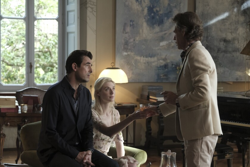 "Claes Bang, Elizabeth Debicki and Mick Jagger in the movie ""The Burnt Orange Heresy."""