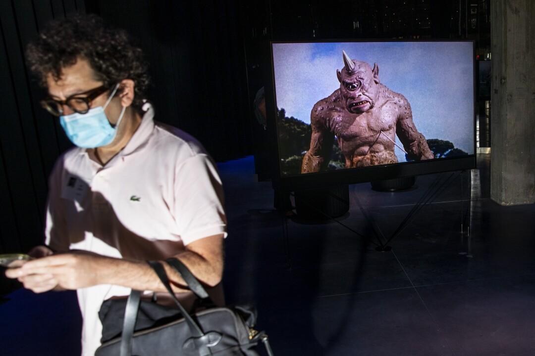 Un visitante pasa por una pantalla con un cíclope.