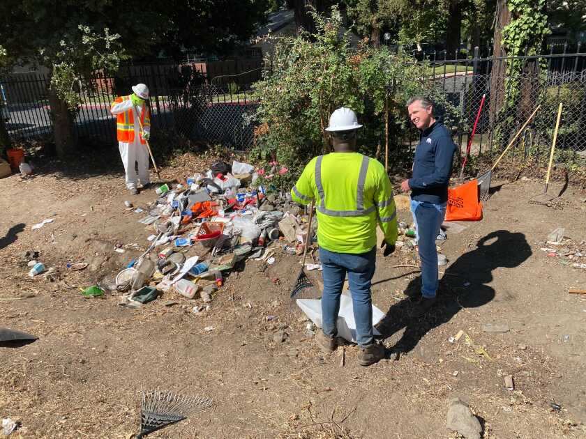 Gov. Gavin Newsom and two workers around a pile of stuff.