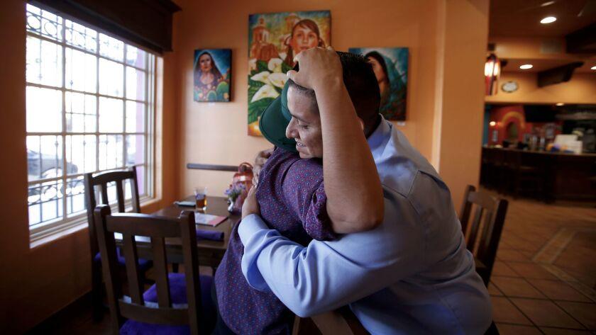 Juan Casas, 28, right, hugs Gloria Plaza, 32, both are DACA participants. Casas has worked the gra
