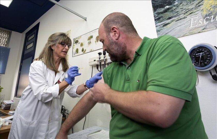 Un hombre recibe la vacuna contra la gripe.