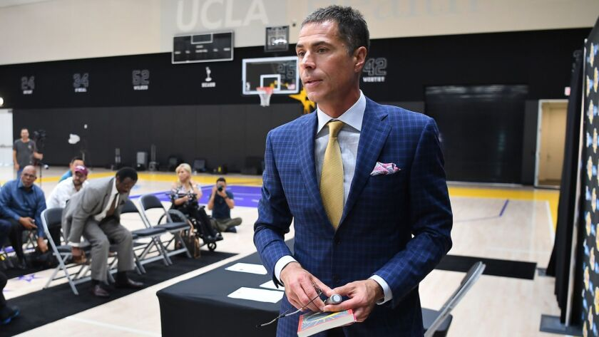 """General manager Rob Pelinka exits the stage in El Segundo after addressing reporters about the Lakers' free-agency acquisitions. """"We celebrate one thing, and that's NBA championships,"""" Pelinka said."""