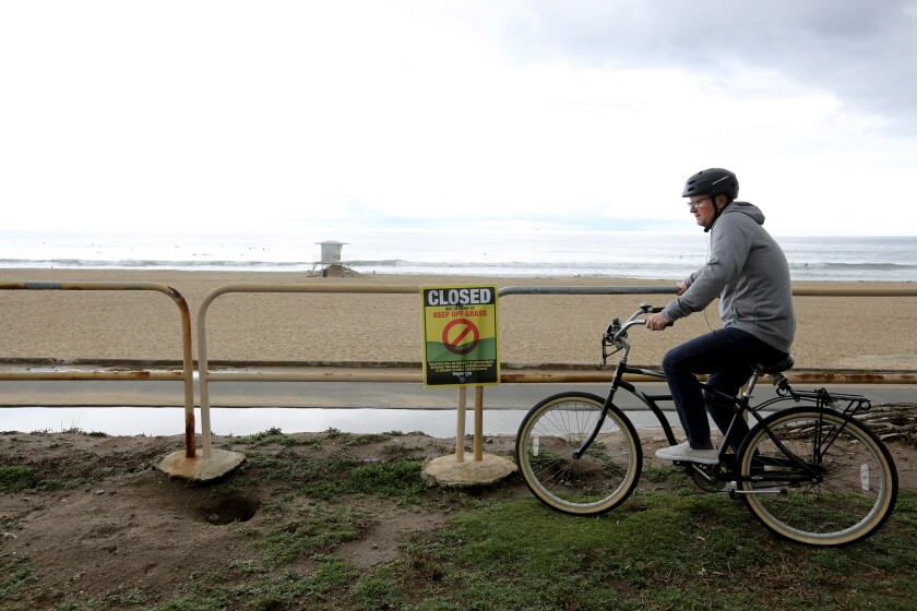 A bicyclist takes a break north of the Huntington Beach Pier on April 10.