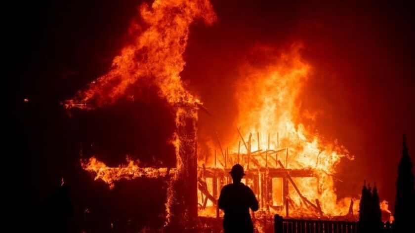 A home burns as the Camp fire rages through Paradise, Calif., on Nov. 8, 2018. Gov. Gavin Newsom wants to tap ratepayers for $10.5 billion to help utilities deal with costs they face when found responsible for igniting wildfires.