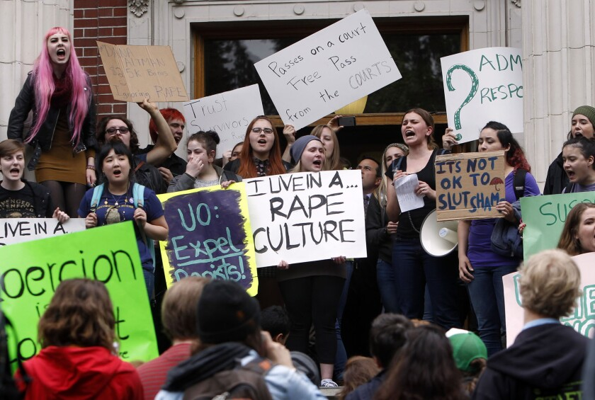 University of Oregon students and staff protest on the steps of Johnson Hall on the school's campus in Eugene, Ore., on Thursday. They gathered days after the release of a police report detailing rape allegations brought by a female student against three basketball players.