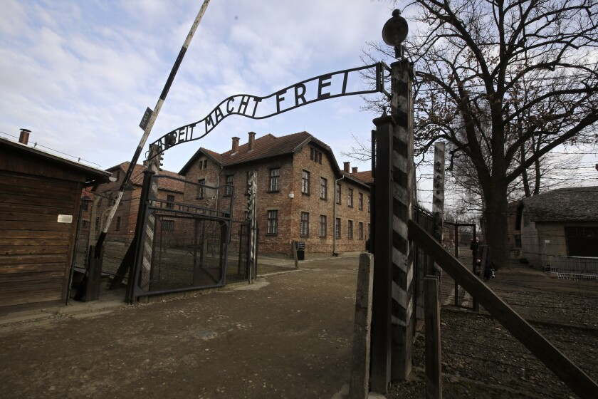 """FILE - In this Jan. 27, 2020 file photo, writing reading in German """"Work Sets You Free"""" is seen on the gate of the Auschwitz Nazi death camp in Oswiecim, Poland. Police and prosecutors in southern Poland were investigating on Wednesday, Oct. 6, 2021, English and German language graffiti found on the barracks of the former Nazi German death camp of Auschwitz-Birkenau. (AP Photo/Markus Schreiber, file)"""