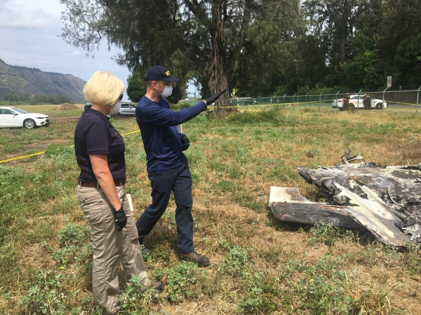 Elliott Simpson, right, briefs Jennifer Homendy at the scene of a plane crash in Waialua, Hawaii.