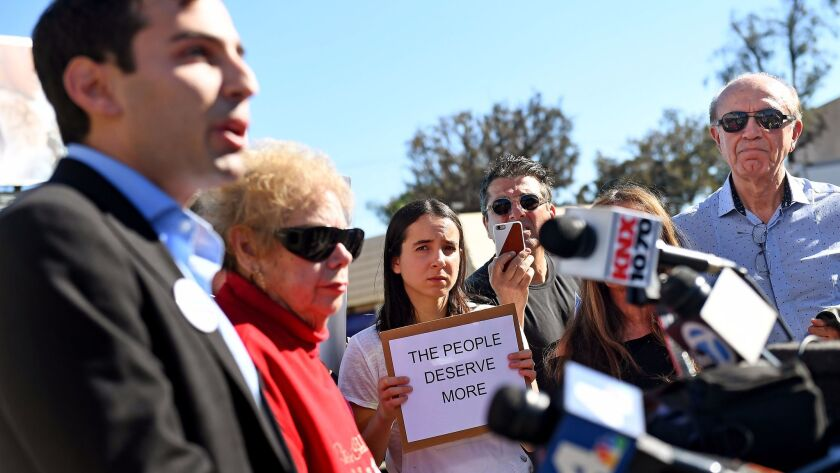 A group of local residents hold a press conference to protest and express community opposition to a Rick Caruso project at the intersection of San Vicente and La Cienega Boulevards on Dec. 29.