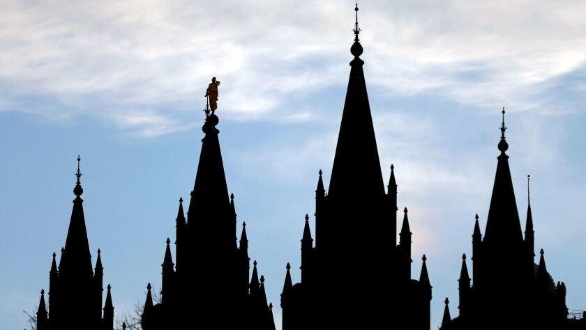 The angel Moroni statue, silhouetted against the sky atop spire second from left, stands atop the Salt Lake Temple, at Temple Squa