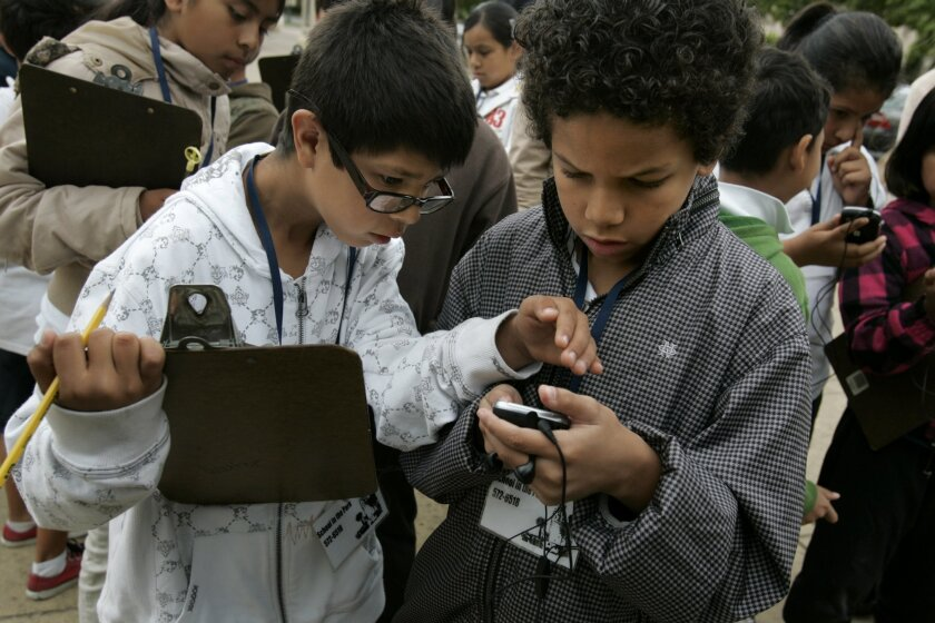 Cesar Cabadas (left) and Antonio Adams, both 10-year-old students at Rosa Parks Elementary School, use smart phones Tuesday at Balboa Park.
