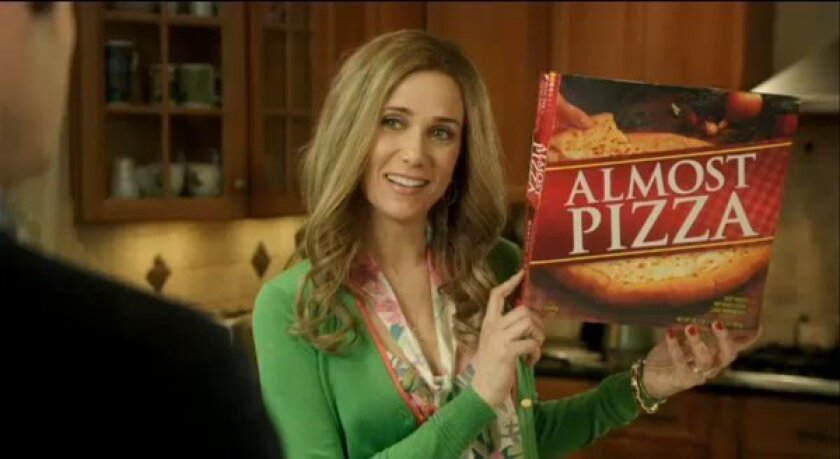 """Kristen Wiig stars in """"Almost Pizza,"""" an SNL spoof of take-and-bake pizza commercials. Still, pizza sales are up."""