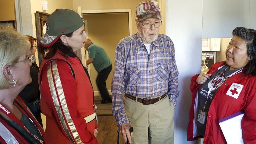 Red Cross volunteers Claudia Warner, Tiffany Bender, and Susan Parker talk with fire survivor Arnold