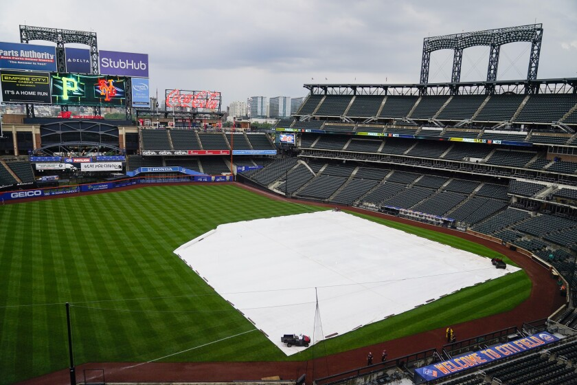 The tarp covers the infield at Citi Field, where the scheduled baseball game between the New York Mets and the Milwaukee Brewers has been postponed, Thursday, July 8, 2021, in New York. The game was rescheduled for Saturday as part of a doubleheader. (AP Photo/Frank Franklin II)