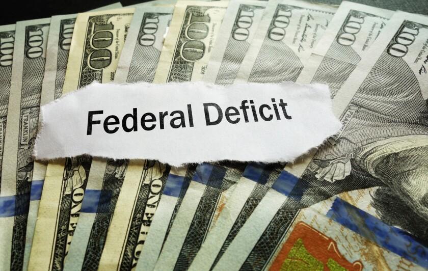 Federal Deficit newspaper headline on hundred dollar bills