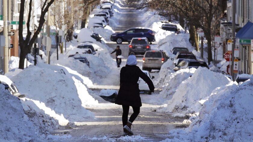 A woman carries a shovel-full of snow down the street to a pile while digging her car out in Boston on Jan. 5, 2018.