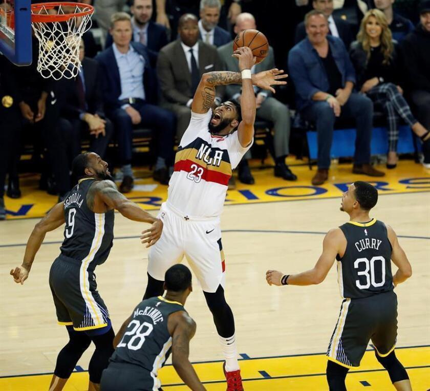 El base de los Warriors de Golden States Andre Iguodala (i) y su compañero Stephen Curry (d) luchan por el balón con el alero de los Pelicans de Nueva Orleans Anthony Davis (c) durante el partido de la NBA entre los Warriors de Golden State y los Pelicans de Nueva Orleans en el Oracle Arena en Oakland, California, Estados Unidos, el 16 de enero de 2019. EFE