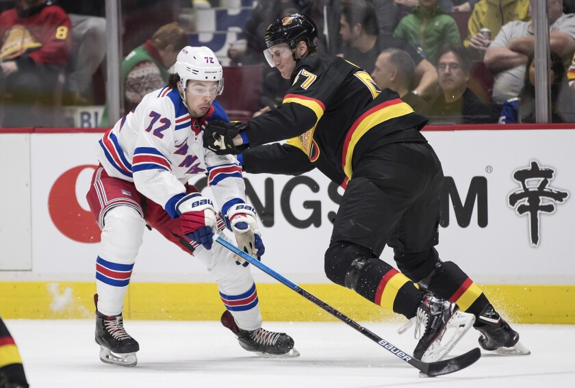 Vancouver Canucks' Tyler Myers, right, checks New York Rangers' Filip Chytil, of the Czech Republic, during the first period of an NHL hockey game Saturday, Jan. 4, 2020, in Vancouver, British Columbia. (Darryl Dyck/The Canadian Press via AP)