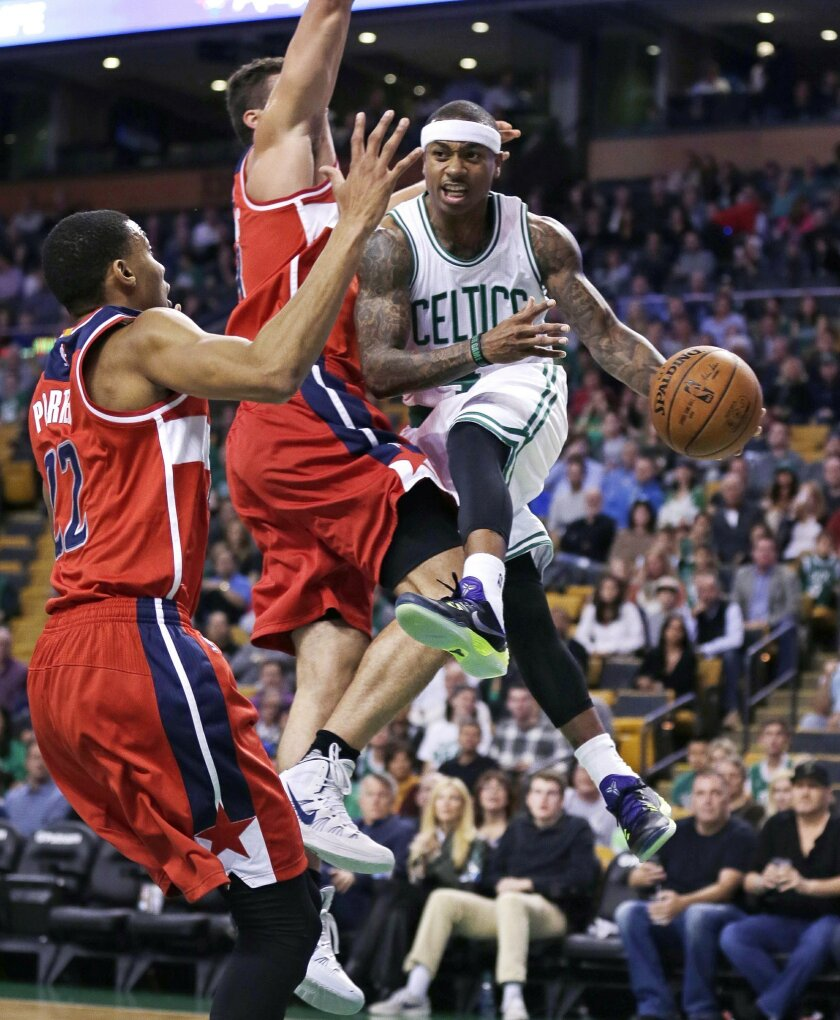Boston Celtics guard Isaiah Thomas, right, looks to pass as he is covered by Washington Wizards forwards Otto Porter Jr. (22) and Kris Humphries, center, during the first quarter of an NBA basketball game in Boston, Friday, Nov. 6, 2015. (AP Photo/Charles Krupa)