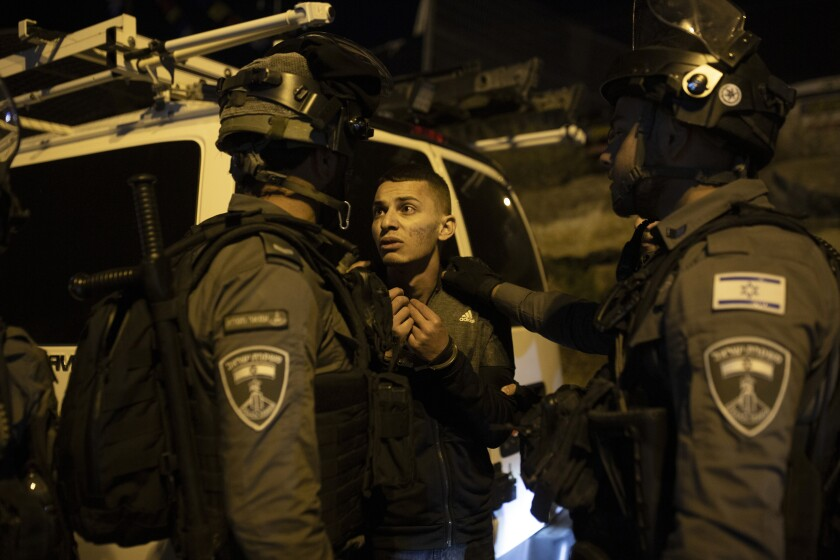 A Palestinian youth pleas with Israeli police after he was detained at a protest against the forcible eviction of Palestinian families from their homes in the Sheikh Jarrah neighborhood of Jerusalem, Thursday, May 6, 2021. Palestinians and Israeli settlers hurled rocks and chairs at each other in Sheikh Jarrah, where dozens of Palestinians are at risk of being evicted following a long legal battle with Jewish settlers trying to acquire property in the neighborhood, which is just north of Jerusalem's Old City. (AP Photo/Maya Alleruzzo)